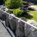 Crest of The Rockery; stones arranged to honor the fallen; Oakes Ames Memorial Hall in background